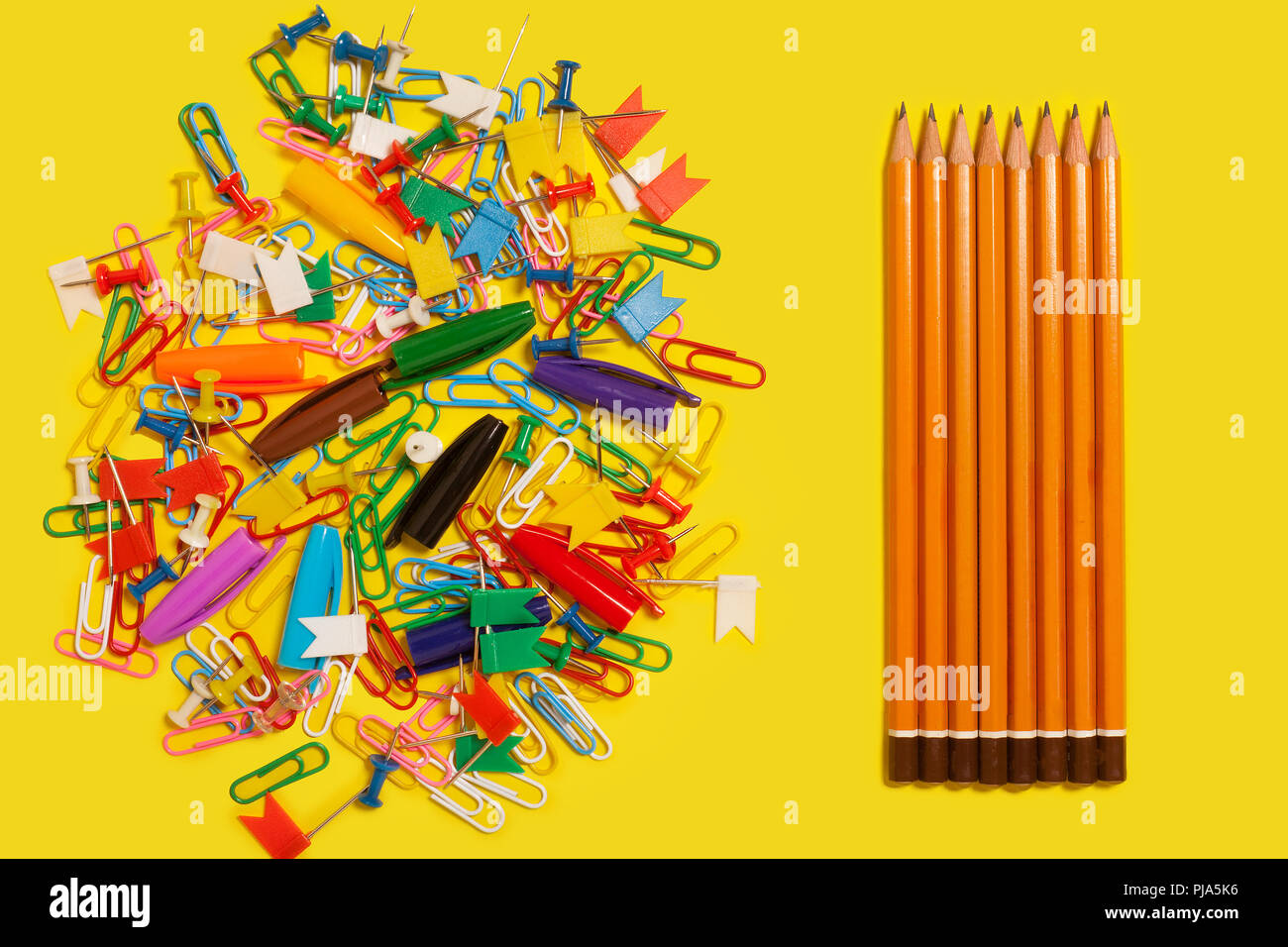 paper clips, pushpins and pen caps near a row of pencils - Stock Image