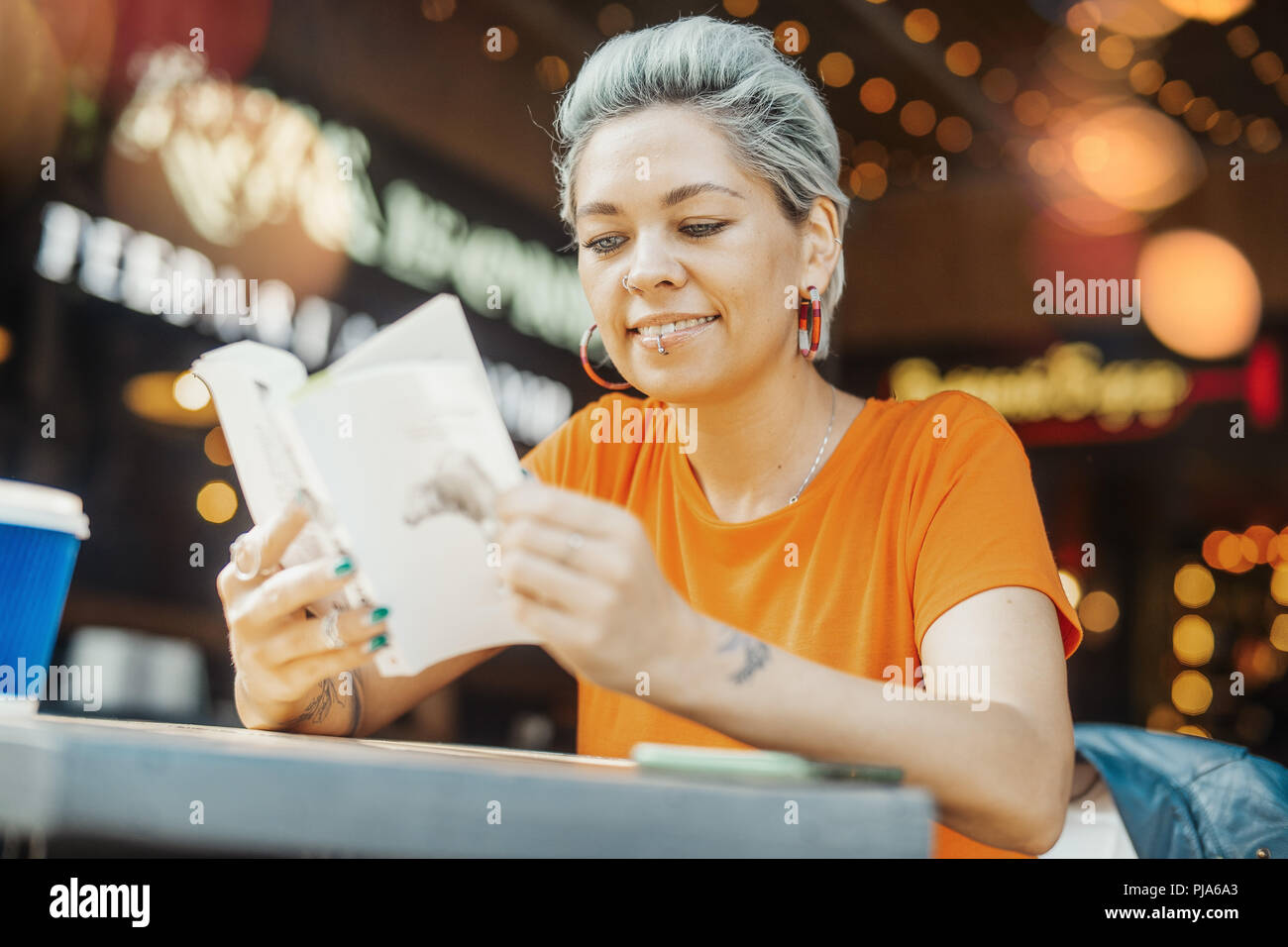 Attractive smiling blonde girl reading book at street cafe and looking aside. - Stock Image