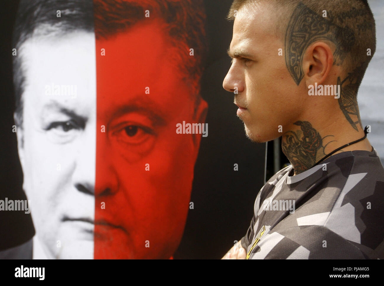 Kiev, Ukraine. 6th Sep, 2018. An Ukrainian activist stands next to a banner with an image which compiled from portraits of the former President Viktor Yanukovich and the current Ukrainian President Petro Poroshenko, during a rally of activists from different political parties with demand of electoral reform in front of the Ukrainain Parliament in Kiev, Ukraine, on 6 September 2018. Credit: ZUMA Press, Inc./Alamy Live News - Stock Image