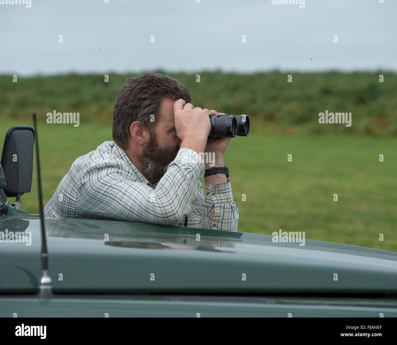 man using binoculars while deer stalking - Stock Image