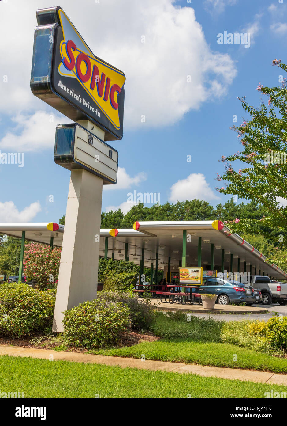 NEWTON, NC, USA-9/2/18:  A Sonic drive-in fast food restaurant, showing a road sign and drive up service. 4 people visible at table under awning. Stock Photo