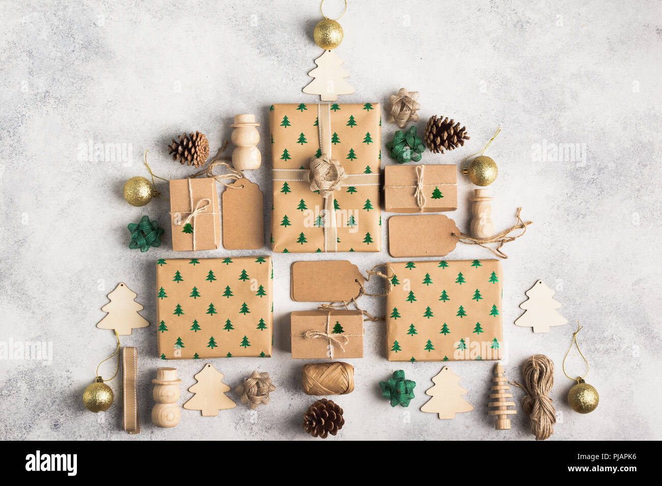 christmas concept christmas tree made up of brown present boxes pine cones golden baubles bows jute twine wooden ornaments on the light backgrou