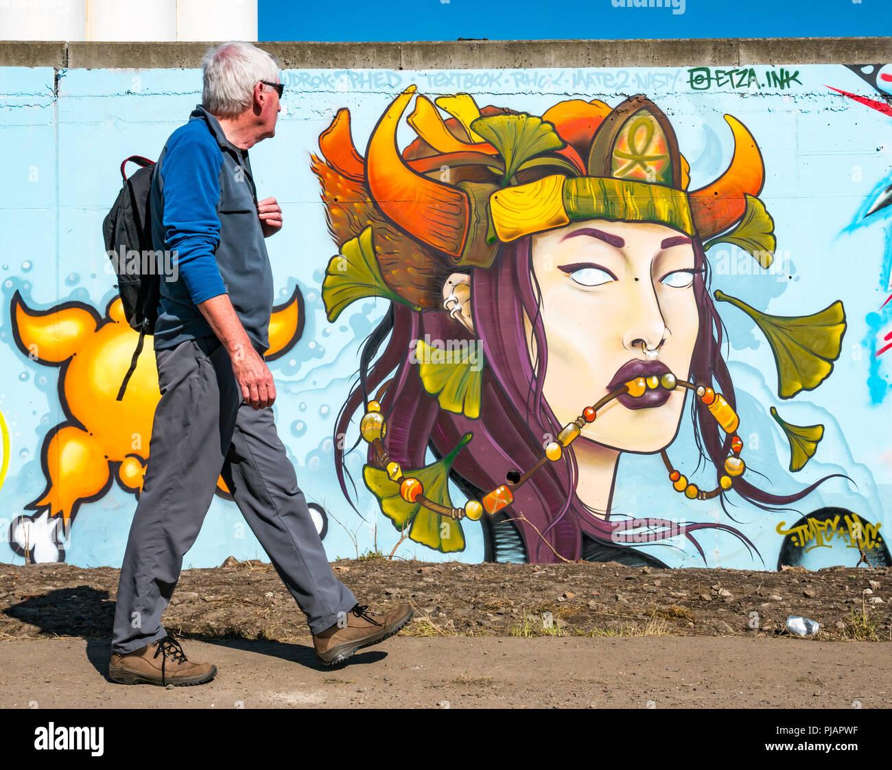 Man walking past female fantasy face rock the dock street art graffiti longest uk