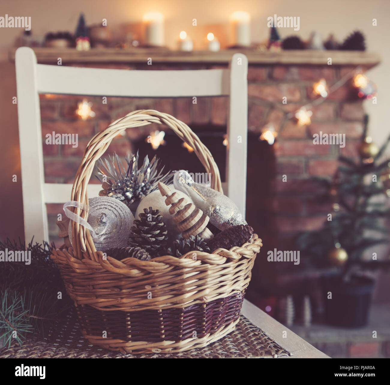 christmas decorations in the in the basket the fireplace on the background with candles an baubles selective focus