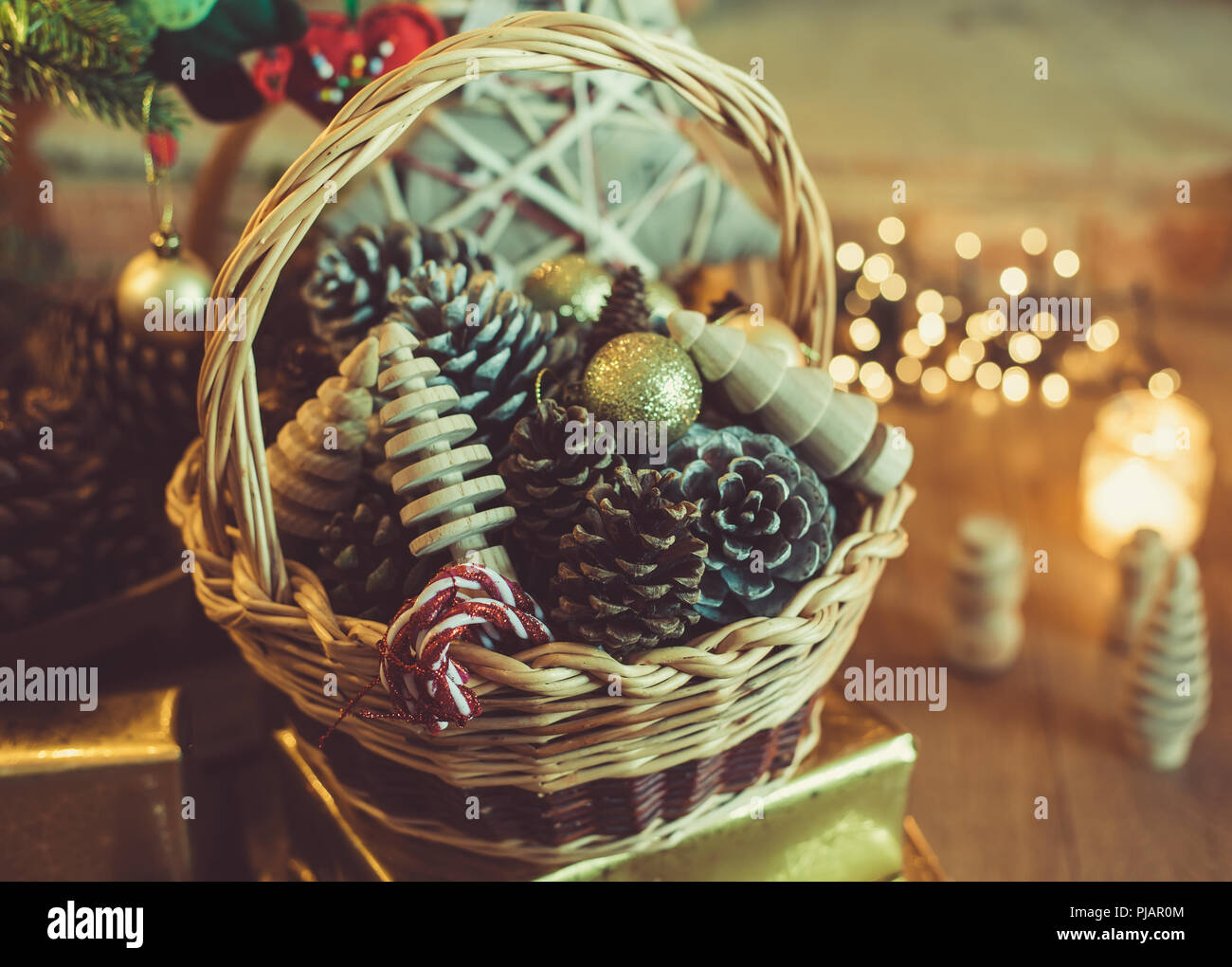 christmas decorations in the basket in front of fireplace with candles and baubles handmade wooden toys made on wood lathe felt ornaments baubles