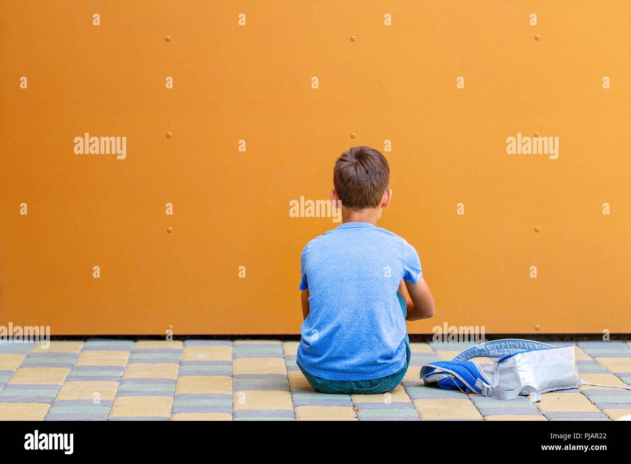 Sad alone boy sitting near colorful wall outdoors