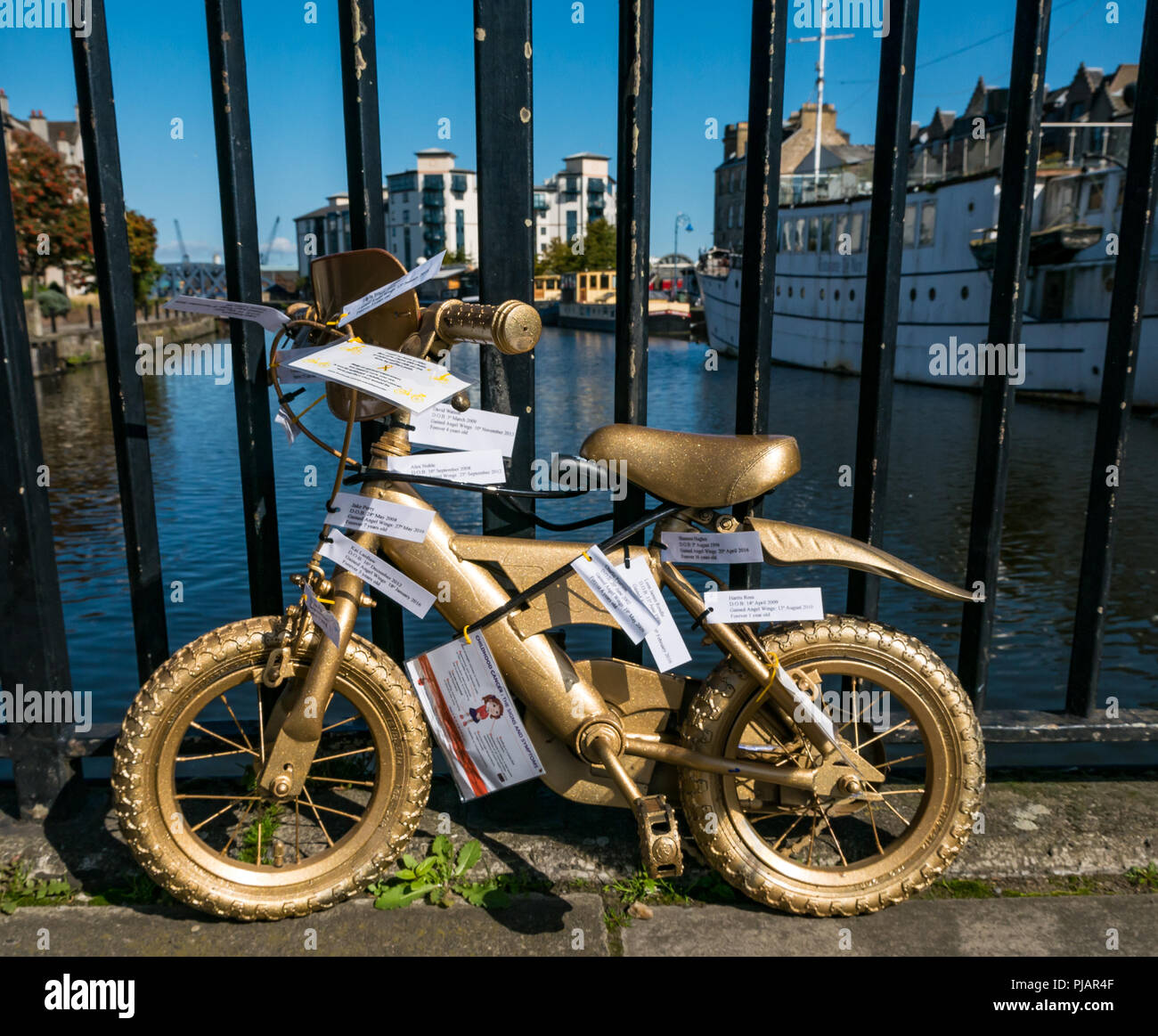 Message on gold painted child's bicycle, The Shore, Leith, Scotland, UK, Glow for Gold September campaign to raise awareness of childhood cancer - Stock Image