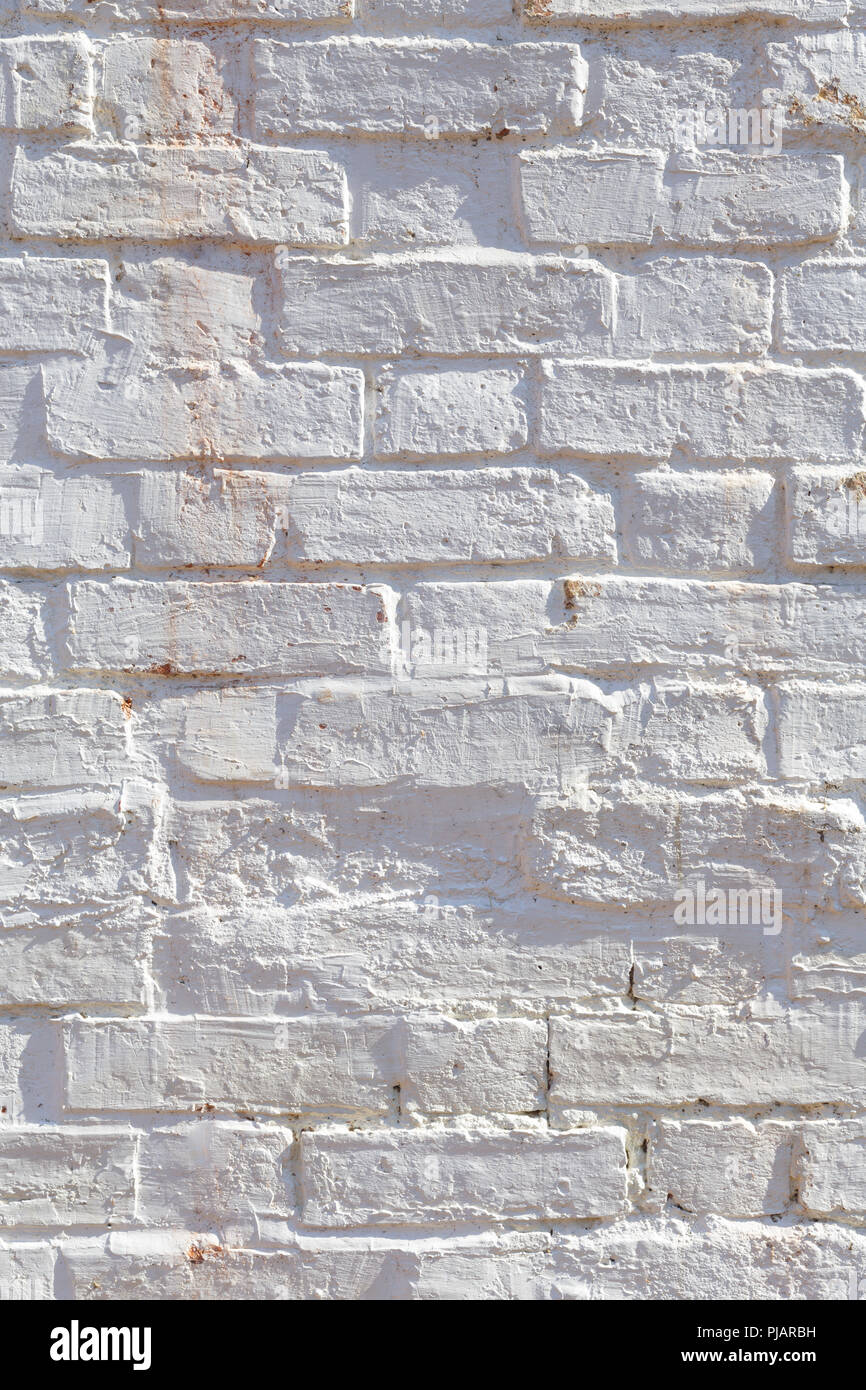 Detail of old brick wall painted white and distressed, peeling and stained. Ideal for grunge background texture - Stock Image