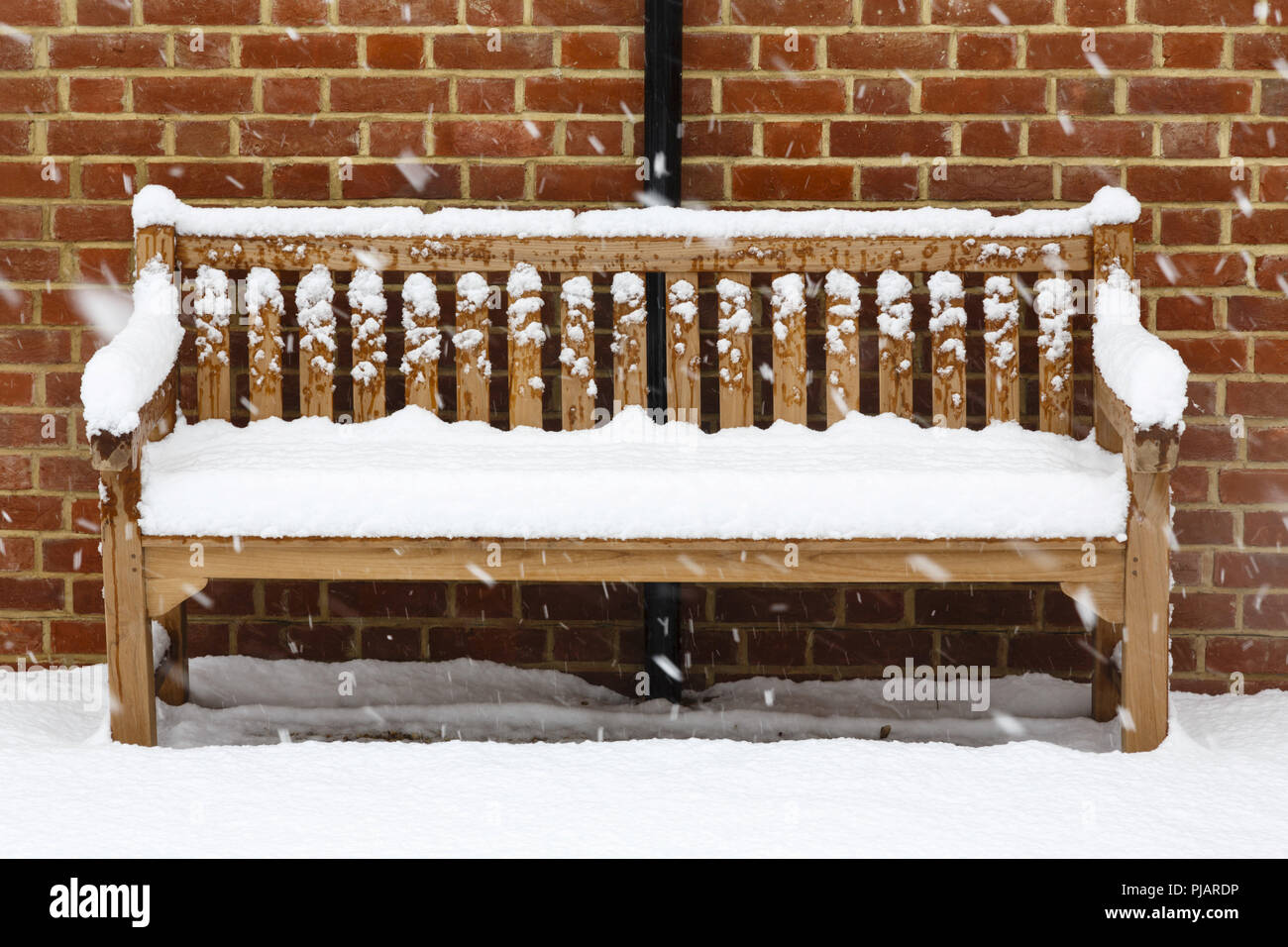 Wooden garden bench covered in snow against a brick wall Stock Photo ...