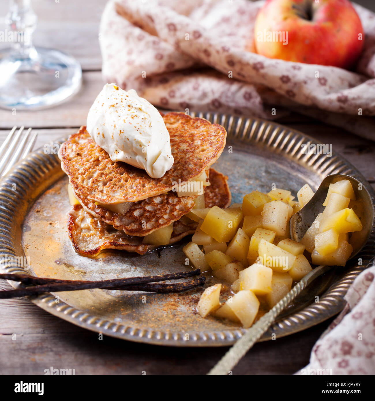 Buckwheat pancakes with poached apples and cream. - Stock Image