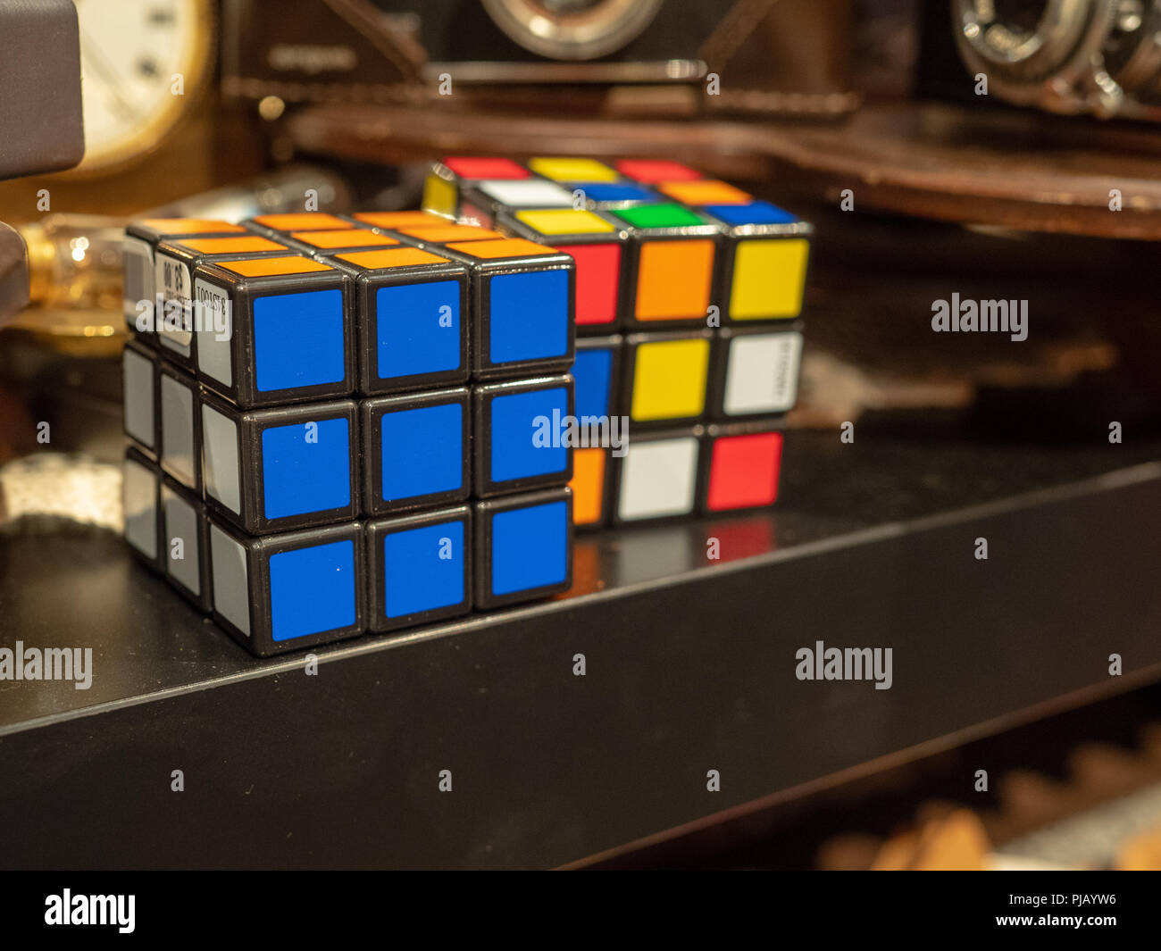 Two Rubik's cubes sitting for sale in an antique store around other oddities  - Stock Image