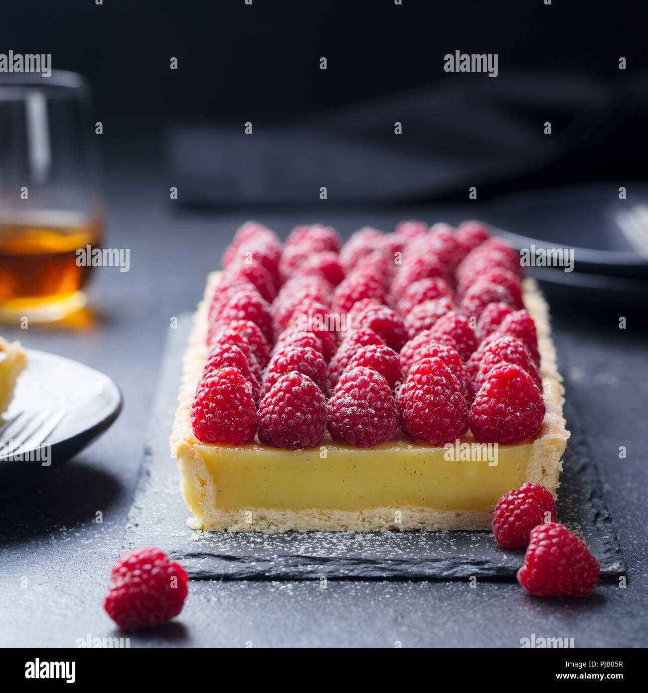 Raspberry tart with vanilla custard and white chocolate on slate board. Black stone background. Copy space. - Stock Image