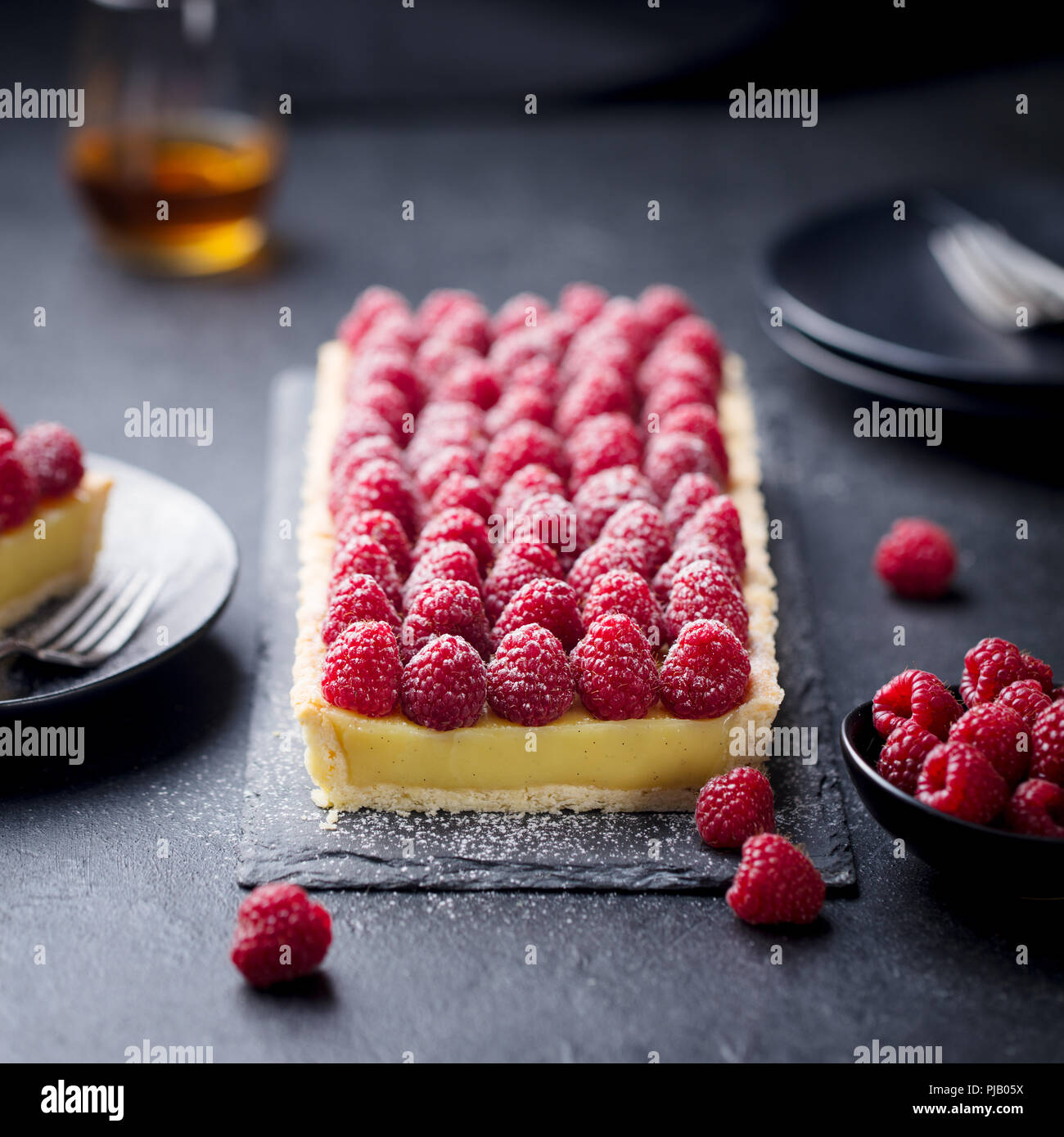 Raspberry tart with vanilla custard and white chocolate on slate board. Black stone background. Stock Photo