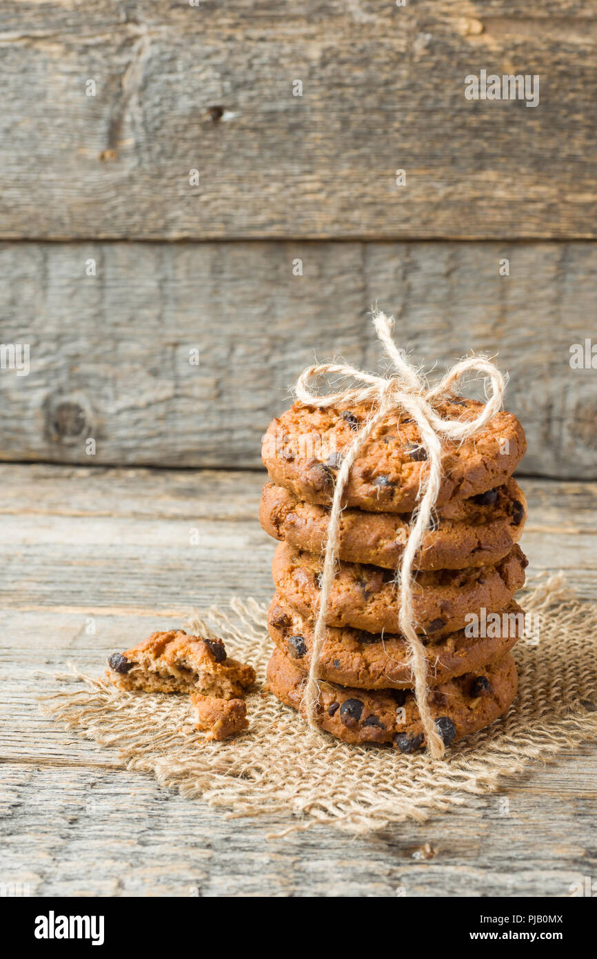 Homemade cookies with chocolate thread tied on a wooden table. - Stock Image