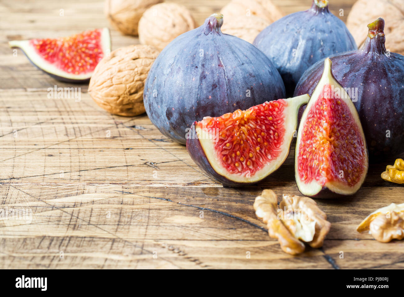 Fresh figs whole and cut with walnut kernels on a wooden old background - Stock Image