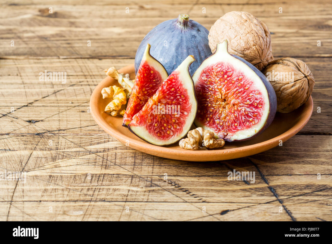 Fresh figs whole and cut kernels of walnuts on a plate the old wooden background Stock Photo