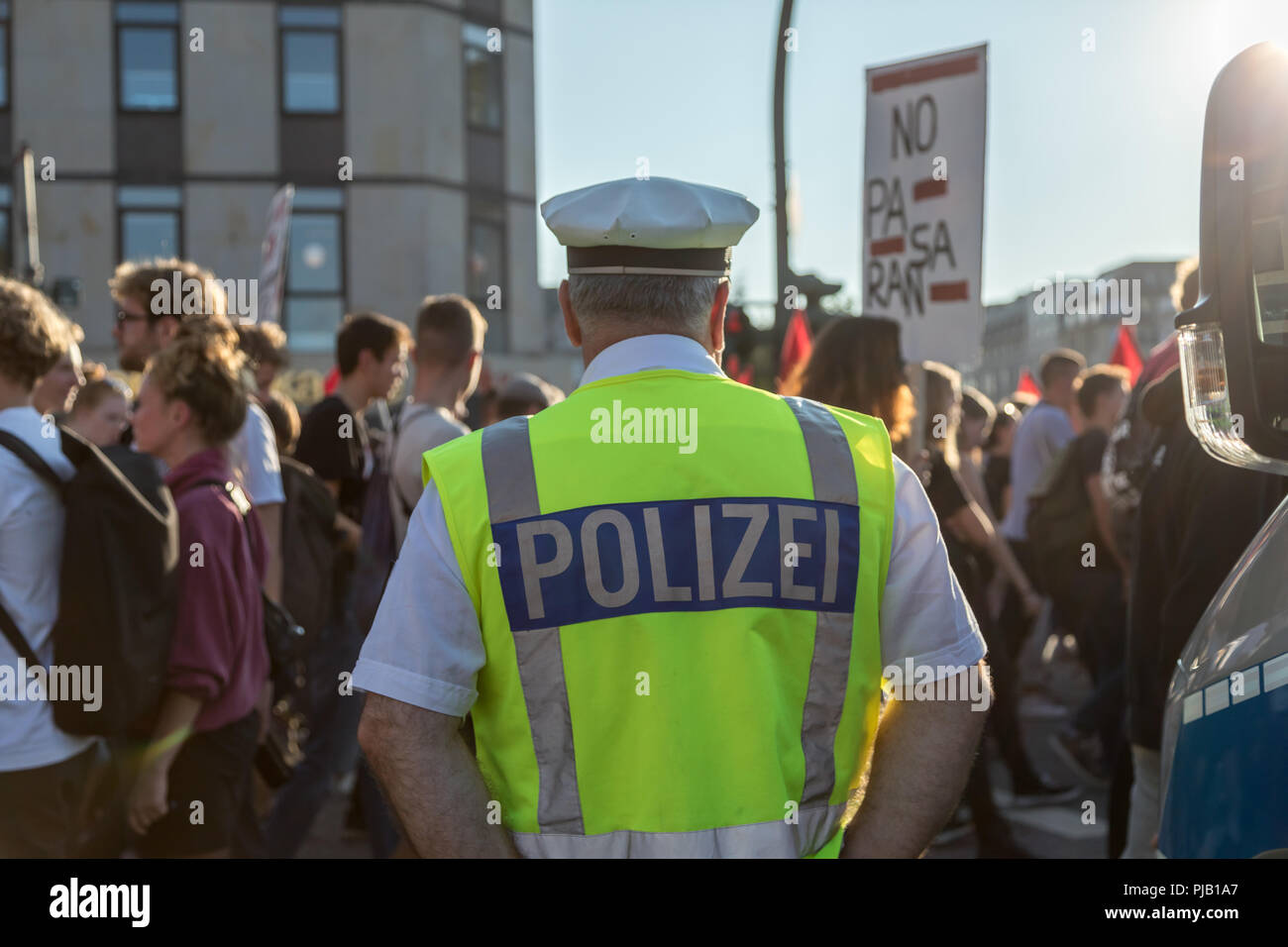 Police officer observing anti racist protestors in Hamburg. 10.000 People demonstrated against a deployment of 176 rascists. - Stock Image