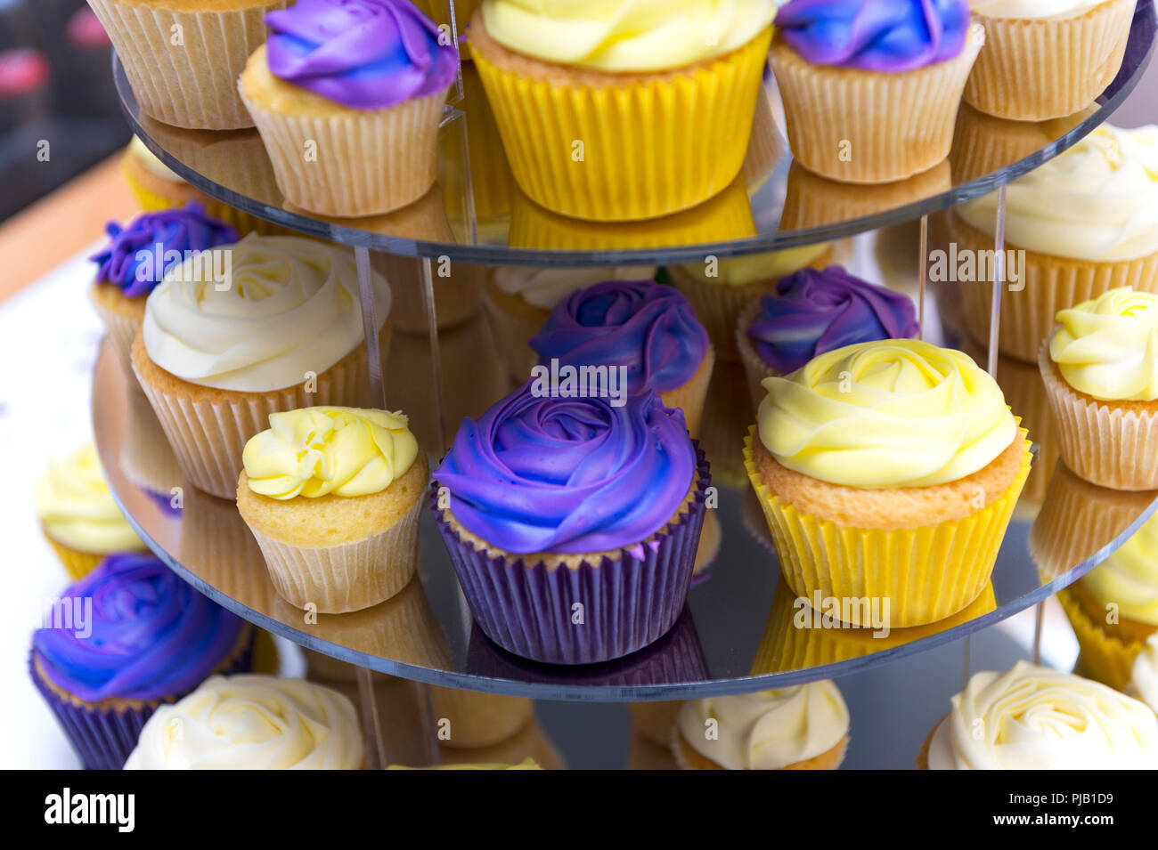 Celebration purple and yellow cupcakes on cake stand for 70th birthday - Stock Image