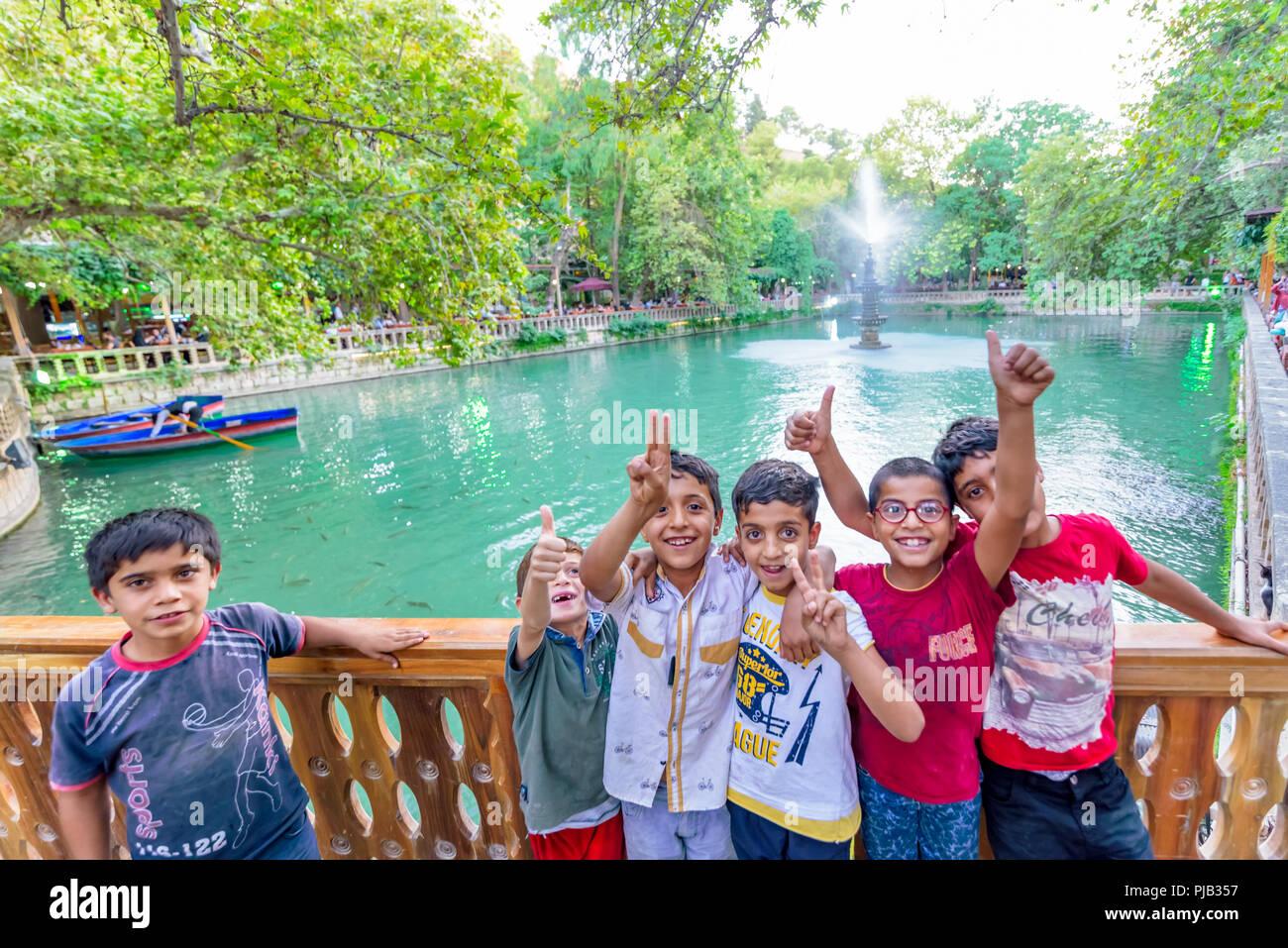 Unidentified children have fun around  Aynzeliha Lake,second sacred pool within Golbasi Park in Sanliurfa.Turkey.18 July 2018 - Stock Image