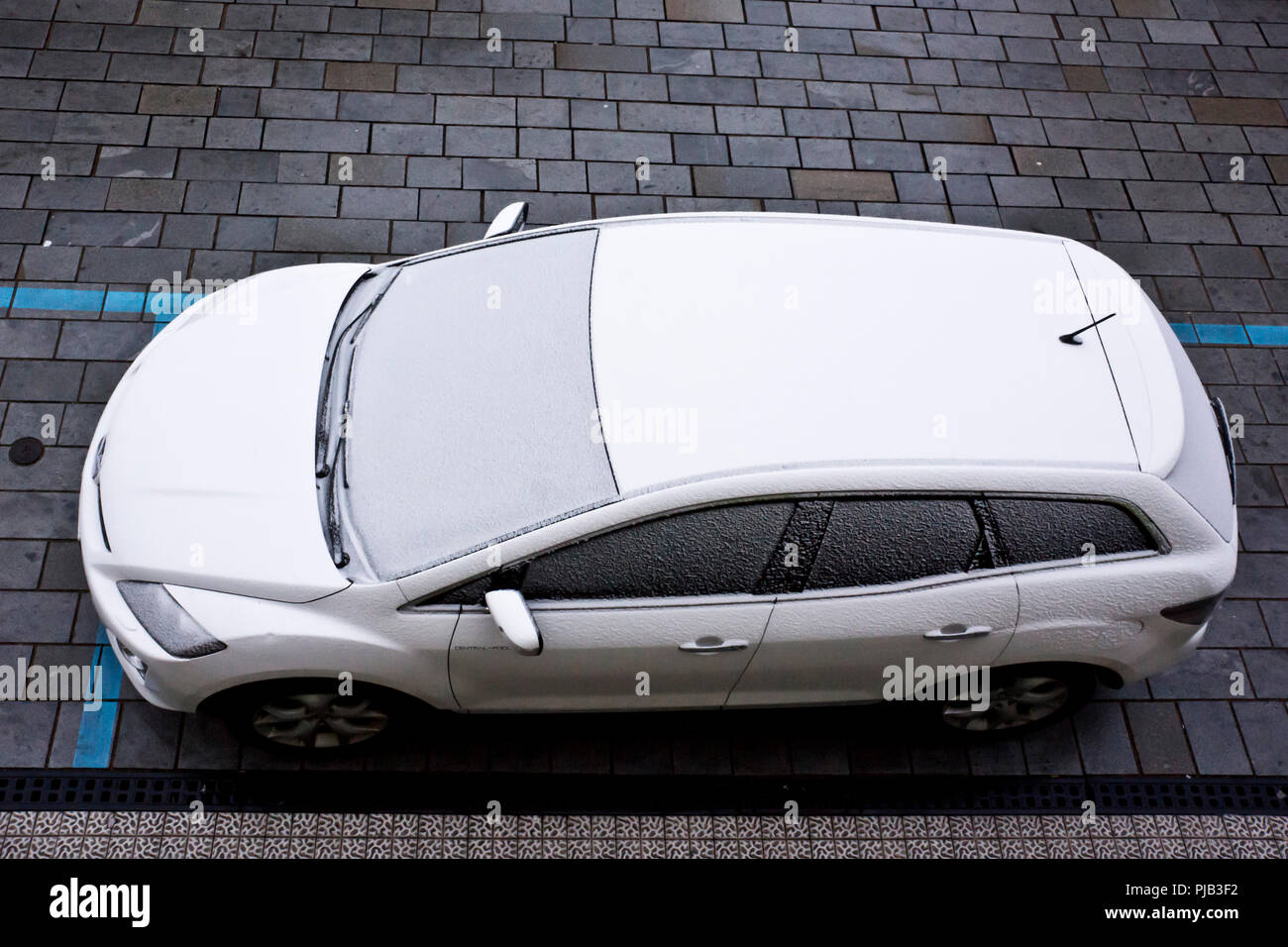 car parked on the street and covered with snow - Stock Image