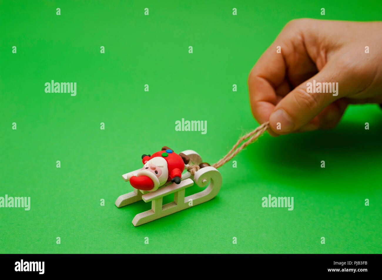 male hand pulling a Santa Claus figurine on a sledge - Stock Image