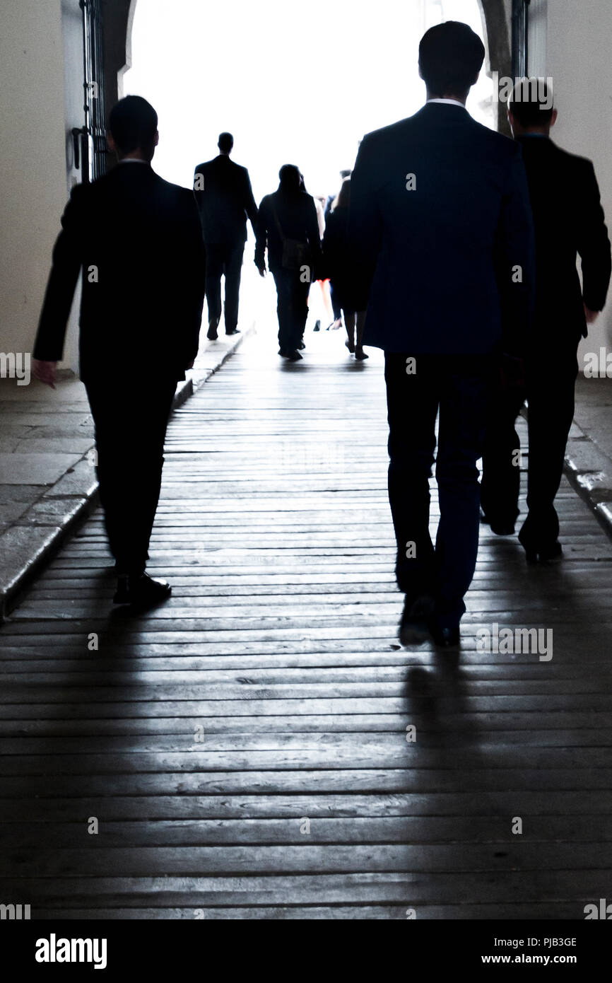 silhouettes of business people walking in an underpass - Stock Image
