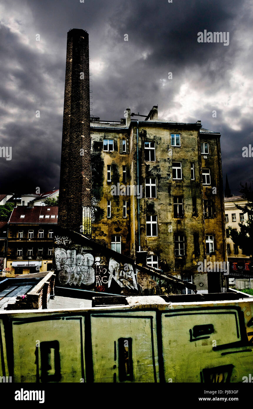 dramatic scene with buildings and industrial chimney in ruin and dark gloomy sky - Stock Image