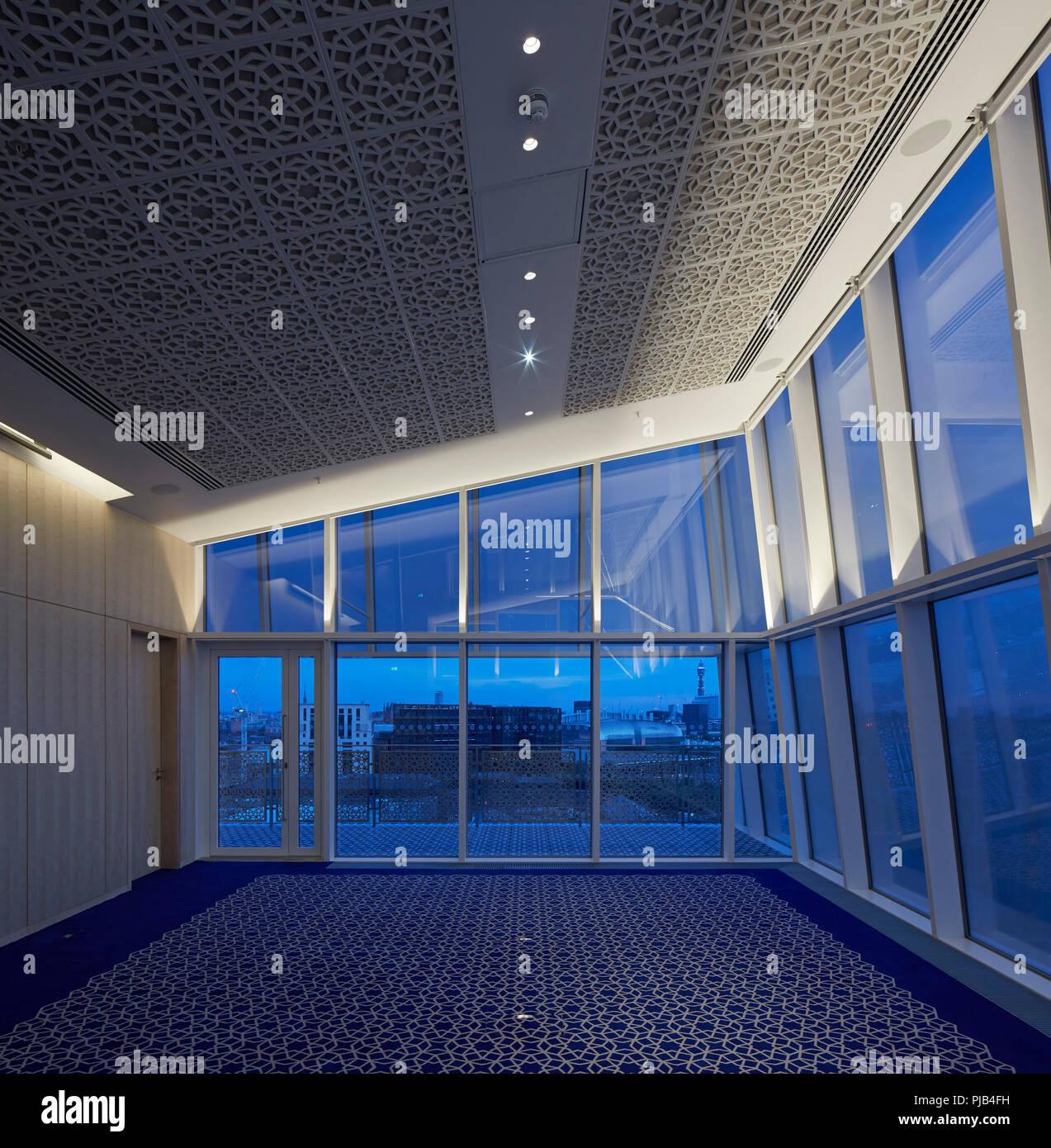 Upper level office interior, viewed at dusk. Aga Khan Centre, London, United Kingdom. Architect: Maki and Associates, 2018. Stock Photo