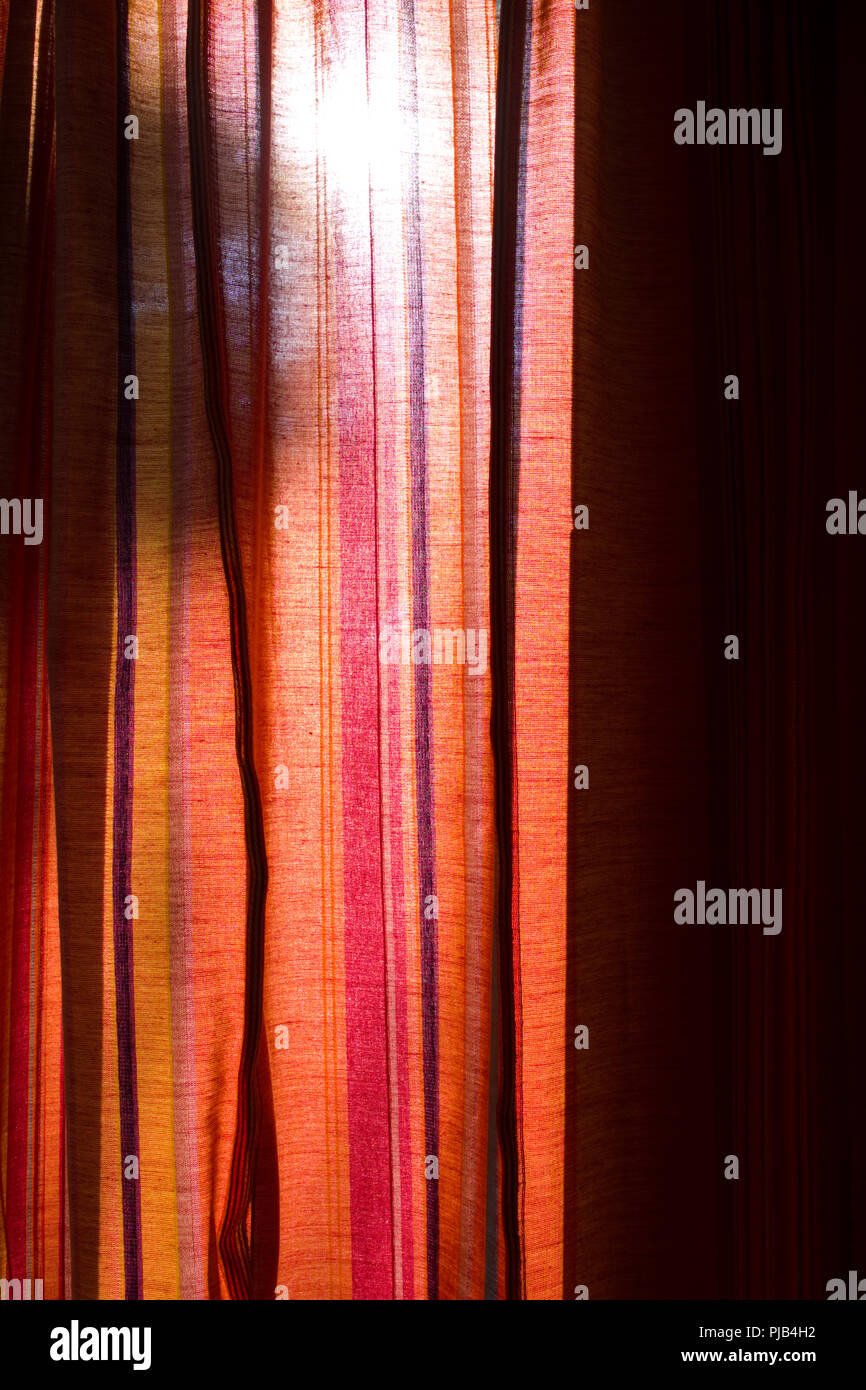photograph of vertically striped red and orange curtains backlight by the early morning sun with ominous shadow of person looming - Stock Image