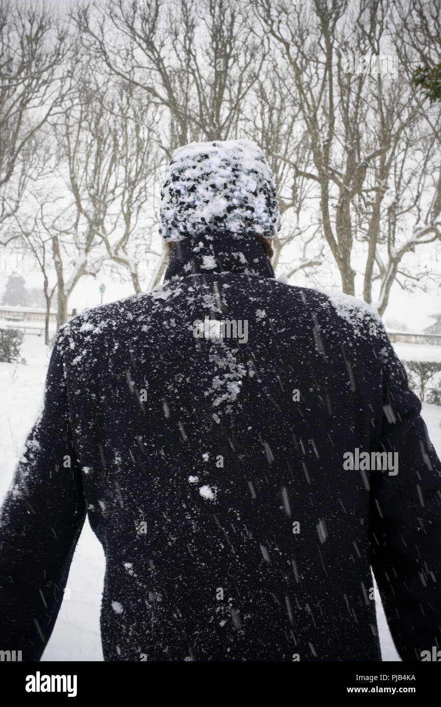 rear view of standing man with overcoat and hat being covered by snow during heavy snowfall in Peyrou promenade, Montpellier, france - Stock Image