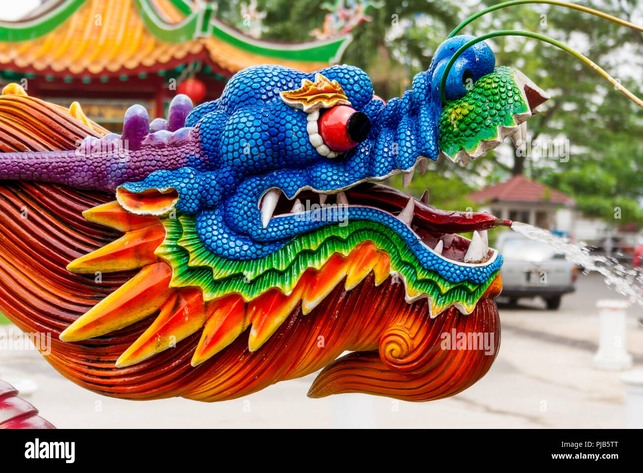 A nice close-up of a colourful water spraying dragon head at a Chinese temple. The water jet comes out of its tongue. - Stock Image