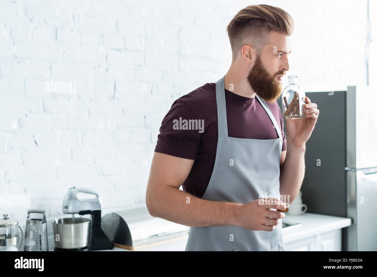 handsome bearded young man in apron holding container with cinnamon sticks in kitchen - Stock Image