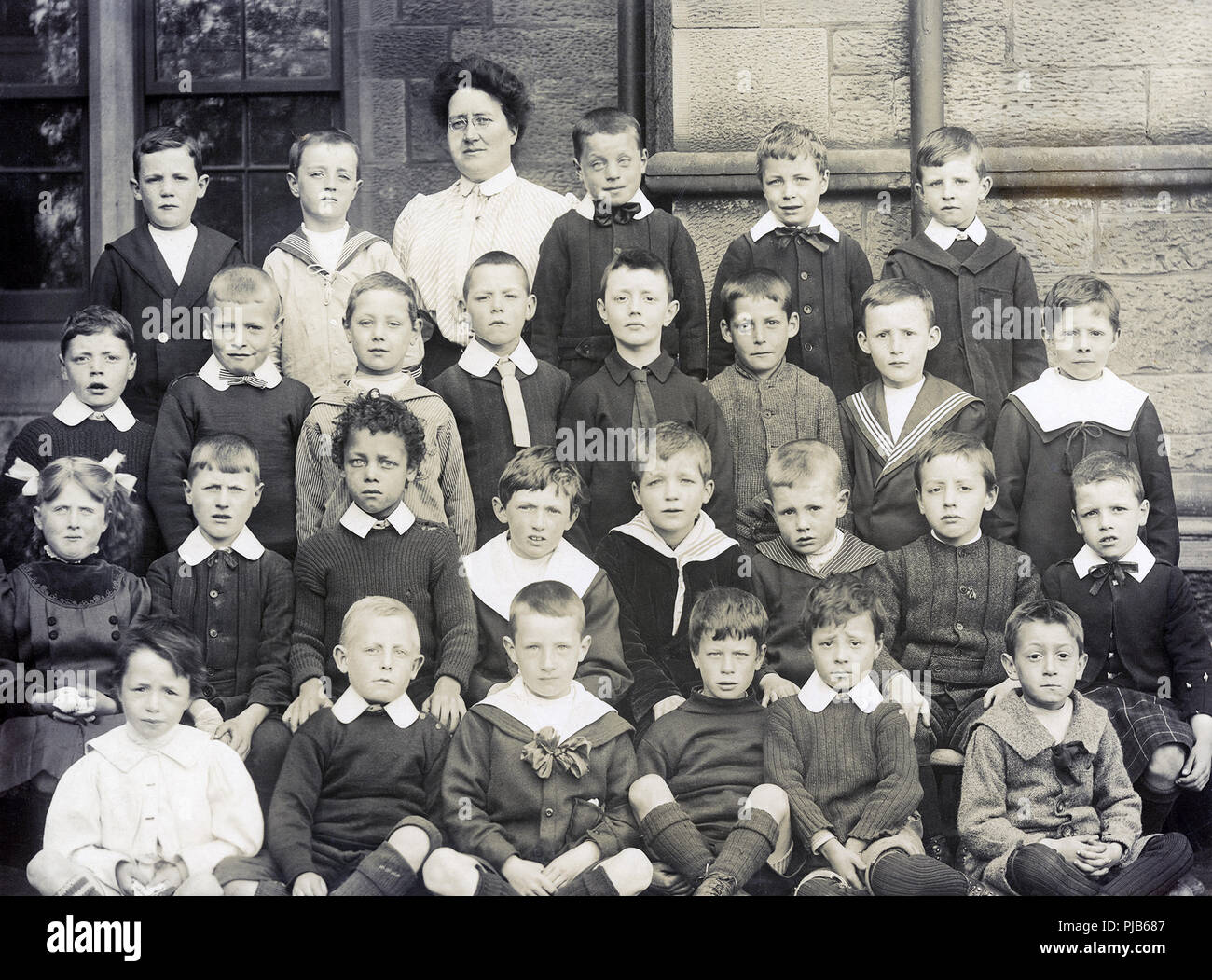 A Victorian or Edwardian class photo of Glasgow school children and their teacher. - Stock Image