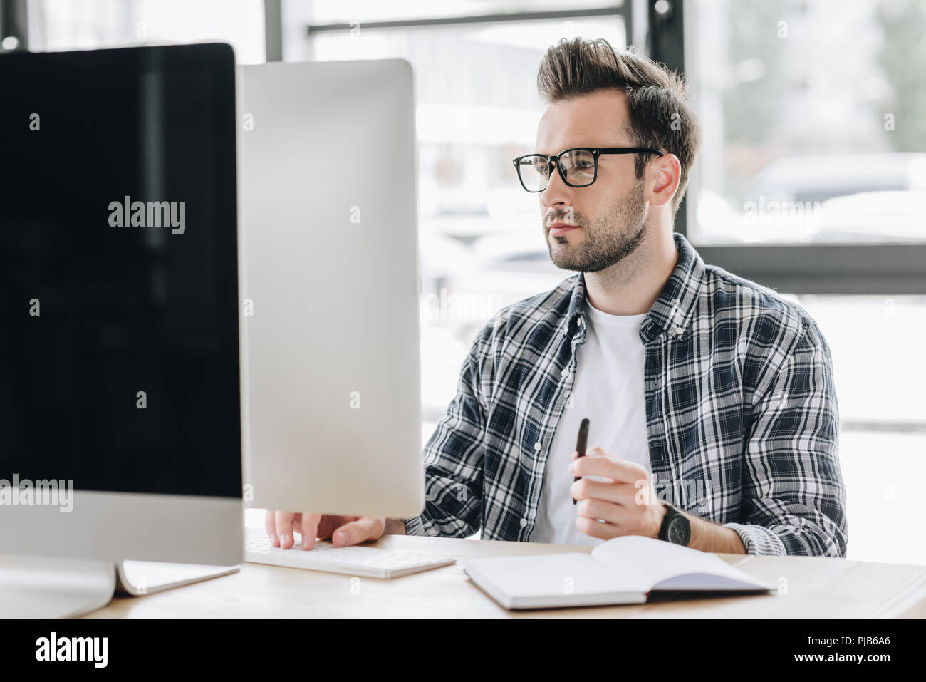 focused young man in eyeglasses working with desktop computer - Stock Image