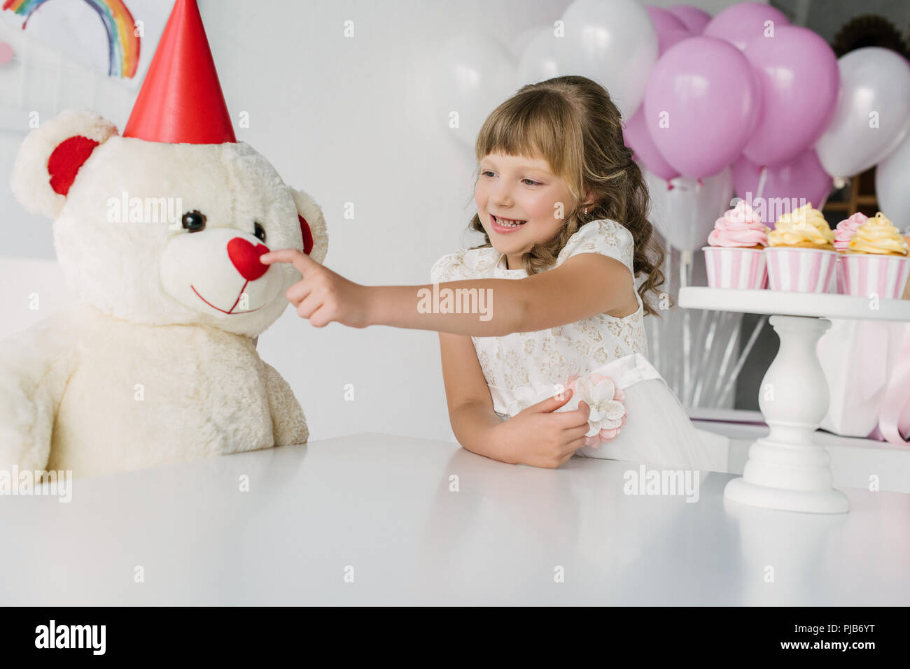 smiling birthday kid touching nose of teddy bear in cone - Stock Image
