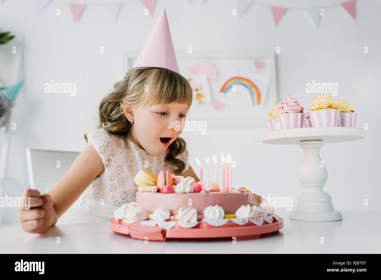 Little Birthday Girl In Cone Blowing Out Candles From Cake On Table