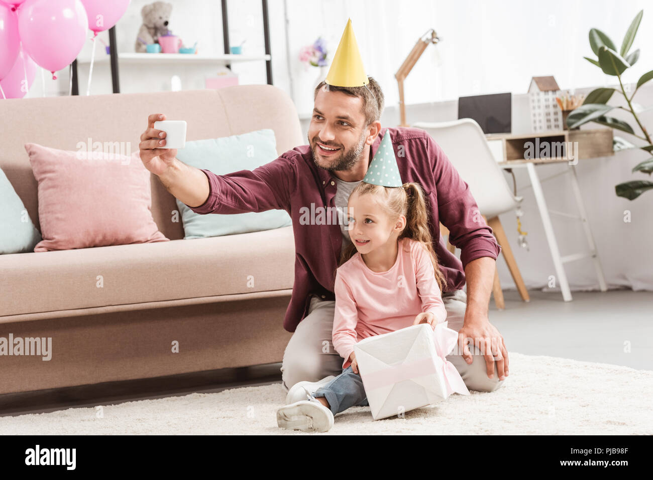 smiling father and daughter in party hats taking selfie with gift for  birthday 8abb1e3e7d9