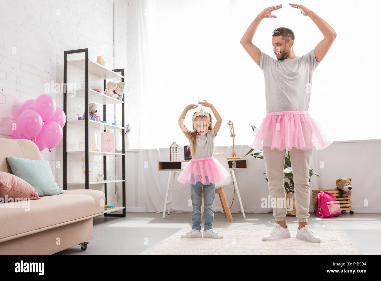 father and daughter in pink tutu skirts dancing like ballerinas - Stock Image
