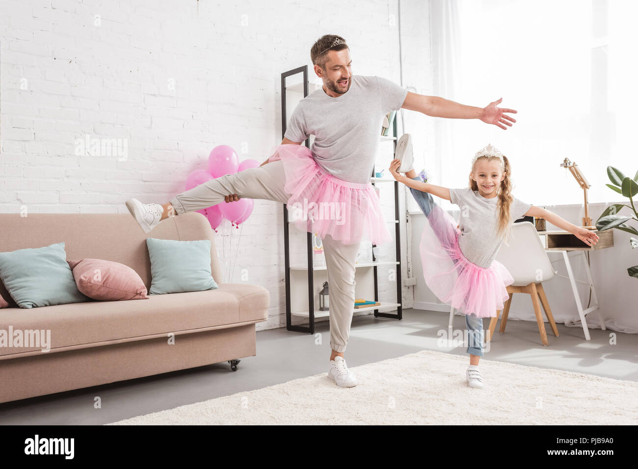 front view of father and daughter in tutu skirts standing on one leg - Stock Image