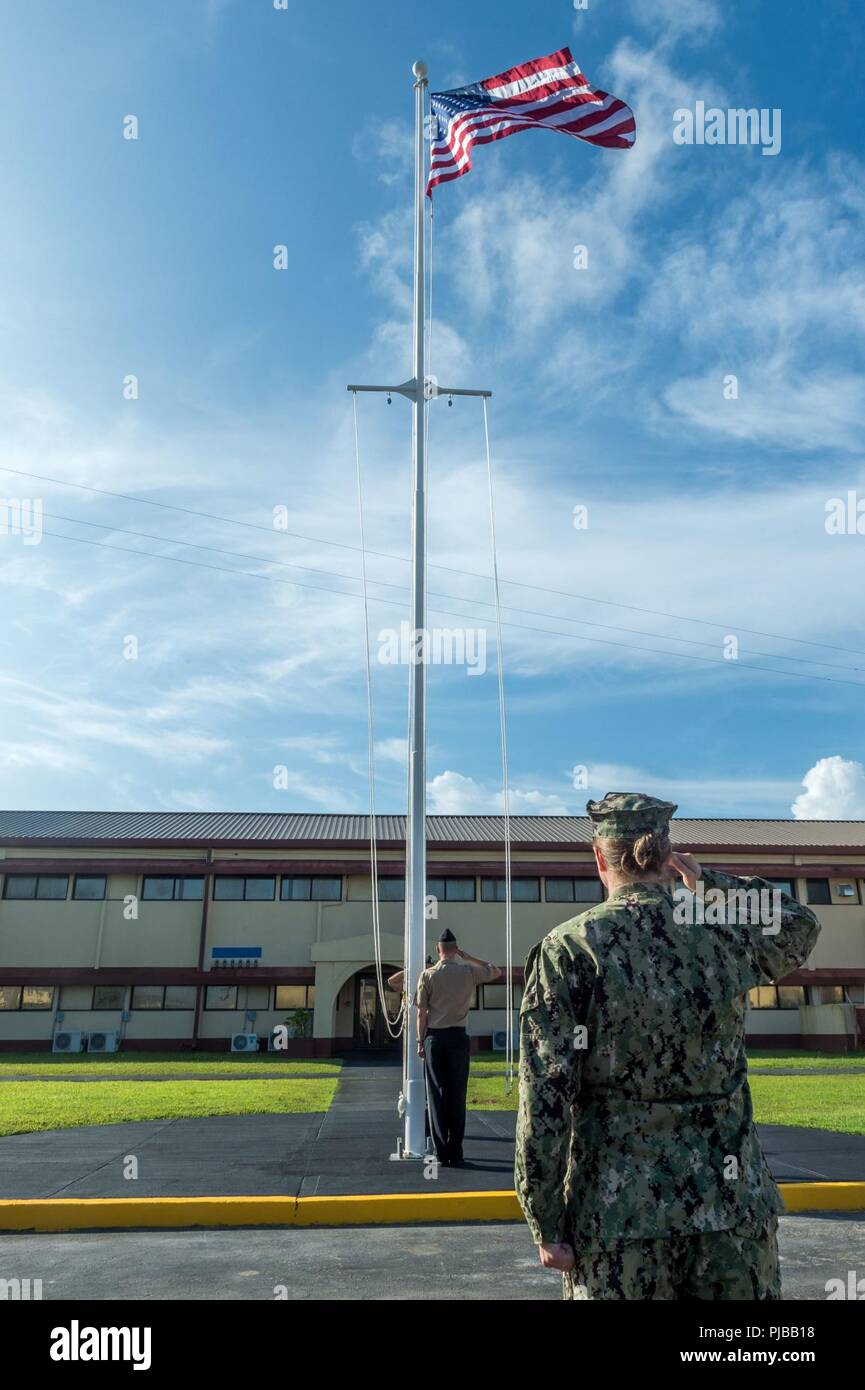 SANTA RITA, Guam (July 1, 2018) Lt. j.g. Elisabeth Staab salutes the American flag during morning colors at 30th Naval Construction Regiment (NCR) headquarters, officially marking its relocation to Guam from Port Hueneme, California. This move streamlines operational effectiveness and establishes the regiment as a forward-deployed operational staff capable of commanding and controlling Naval Construction Force units deployed to the 7th Fleet area of operations. Stock Photo