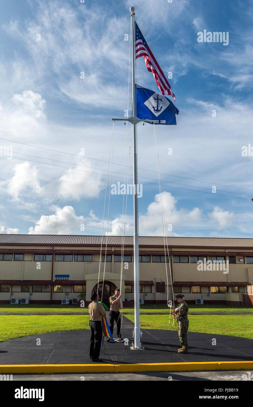 SANTA RITA, Guam (July 1, 2018) Sailors hoist the 30th Naval Construction Regiment (NCR) command flag above its new headquarters officially marking its relocation to Guam from Port Hueneme, California. This move streamlines operational effectiveness and establishes the regiment as a forward-deployed operational staff capable of commanding and controlling Naval Construction Force units deployed to the 7th Fleet area of operations. - Stock Image