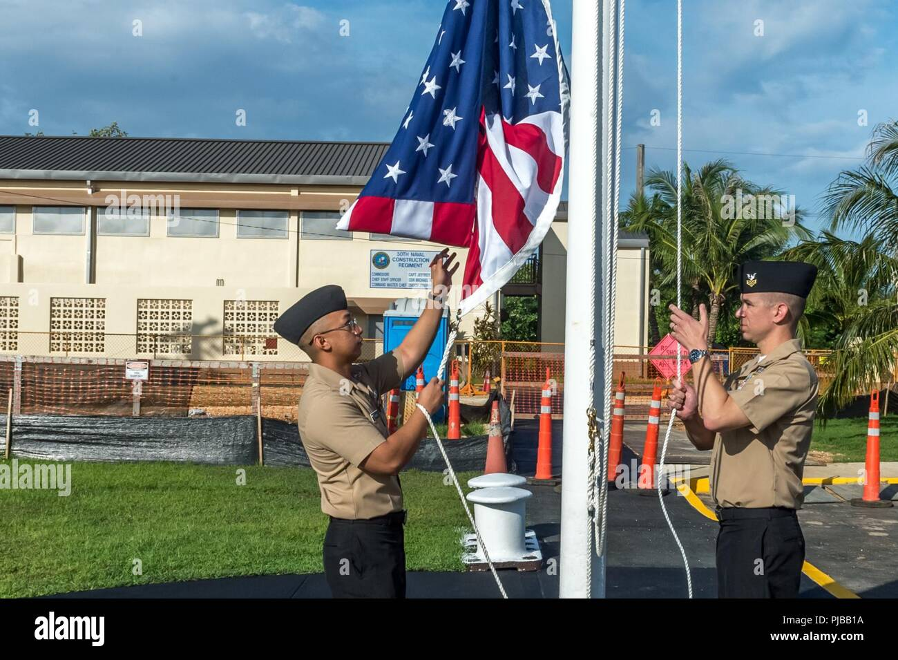 SANTA RITA, Guam (July 1, 2018) Yeoman 1st Class Travis Aquino, left, and Equipment Operator 1st Class Clinton Burch raise the American flag over the 30th Naval Construction Regiment (NCR) headquarters, officially marking its relocation to Guam from Port Hueneme, California. This move streamlines operational effectiveness and establishes the regiment as a forward-deployed operational staff capable of commanding and controlling Naval Construction Force units deployed to the 7th Fleet area of operations. Stock Photo