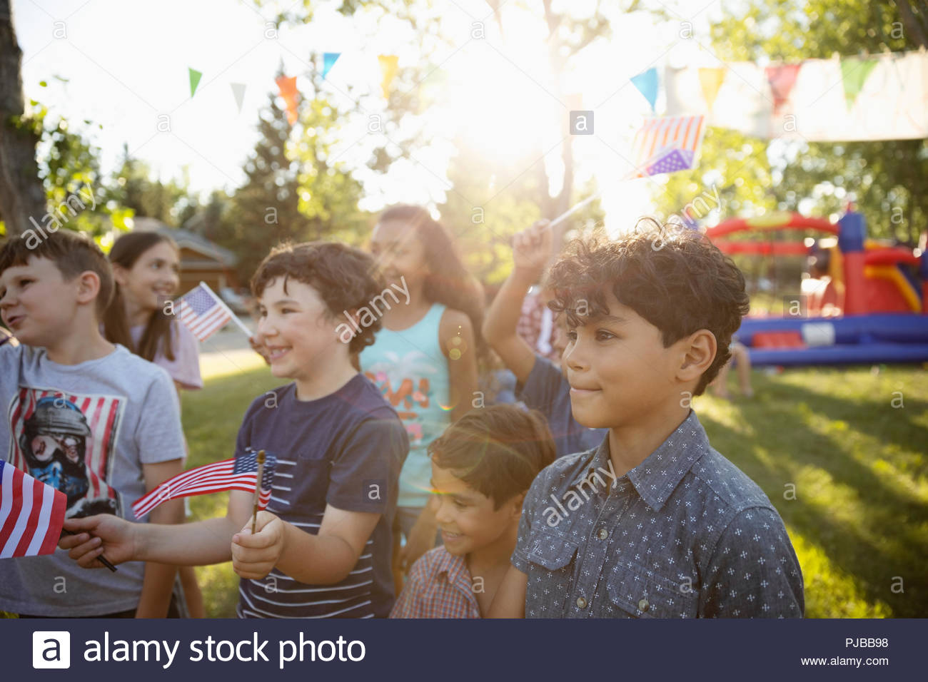 Kids waving American flags at 4th of July summer neighborhood block party in sunny park - Stock Image