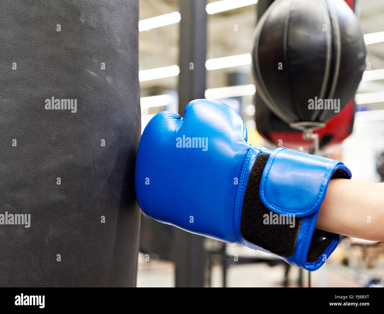 Hand of a child in a boxing glove and punching bag - Stock Image