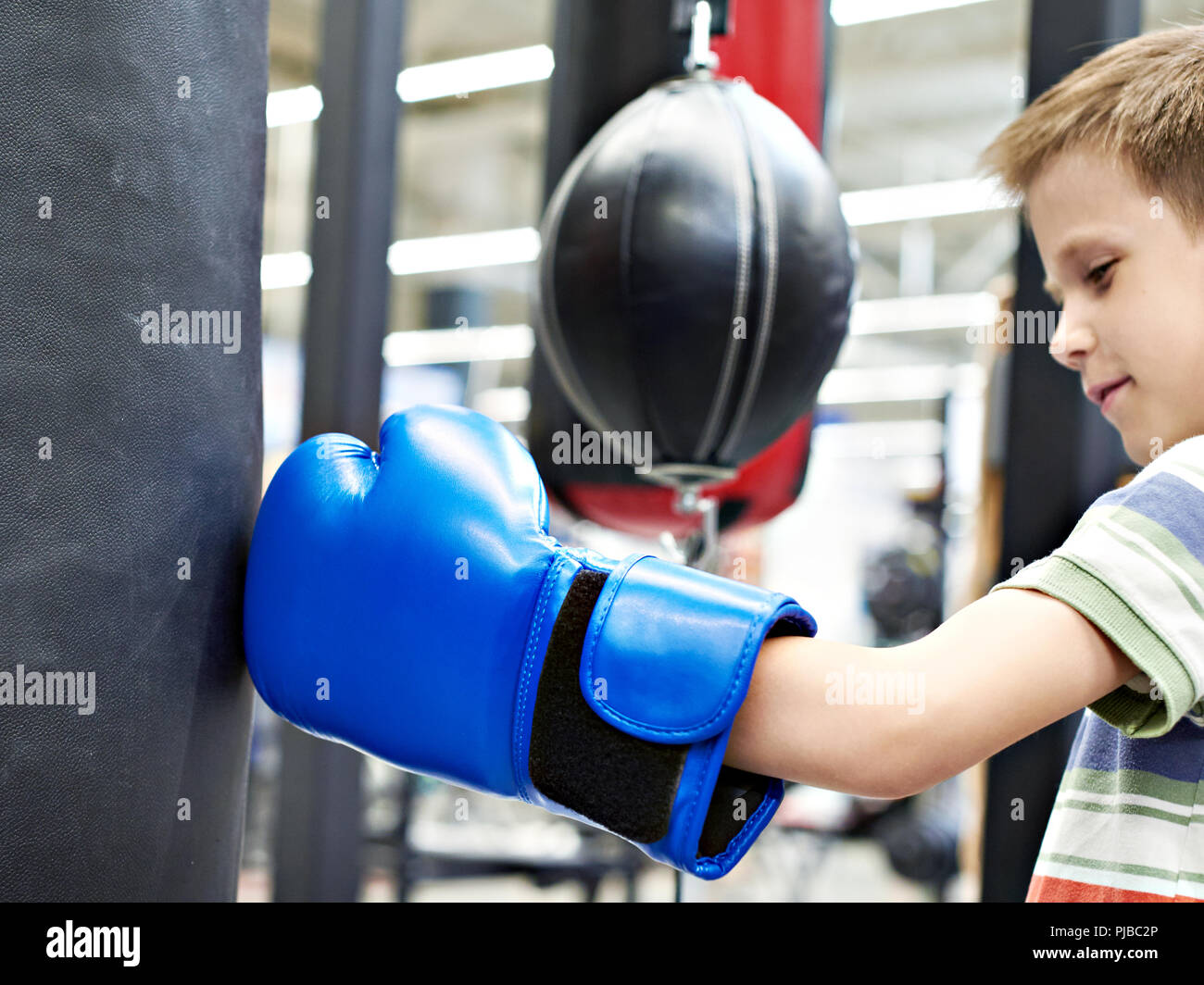 Boy in a boxing glove and punching bag - Stock Image