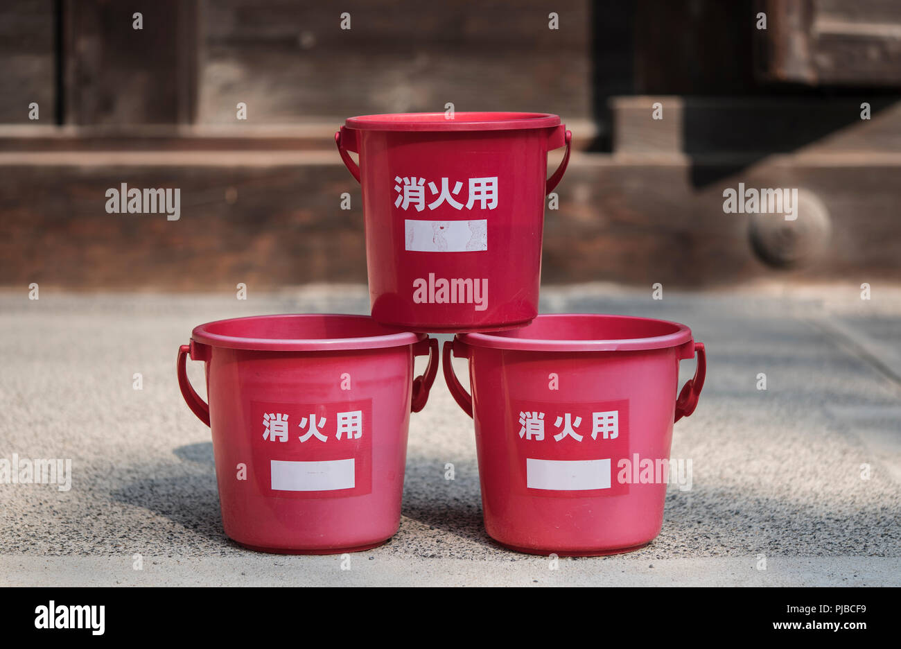 Japanese traditional fire prevention water red platic bucket in front of a wooden temple. Stock Photo
