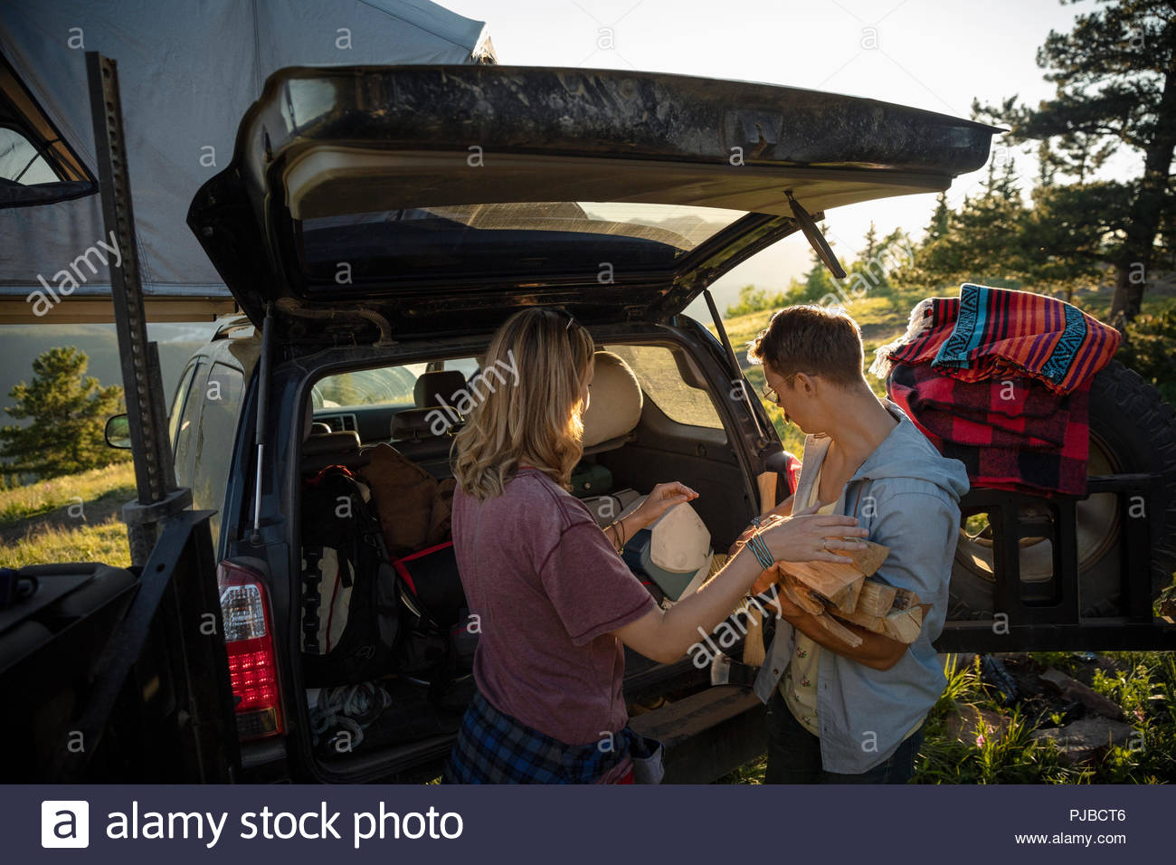 Couple camping, unloading SUV - Stock Image