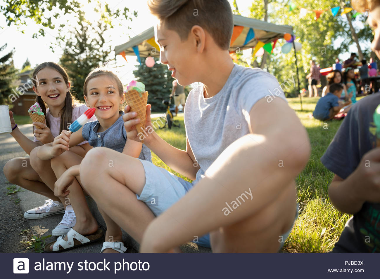 Kids eating ice cream cones and flavored ice at summer neighborhood block party in park - Stock Image