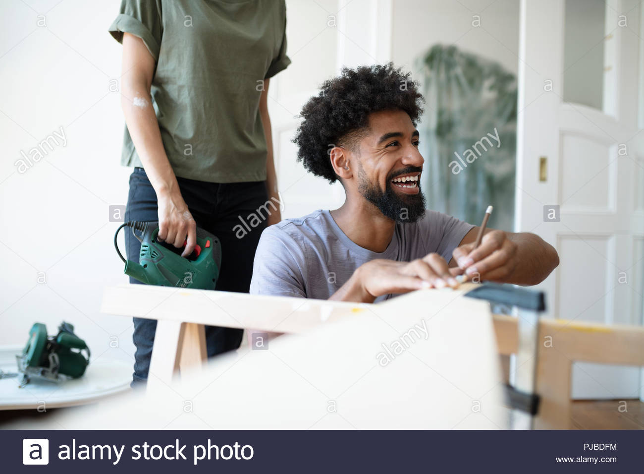 Laughing man doing DIY carpentry project - Stock Image