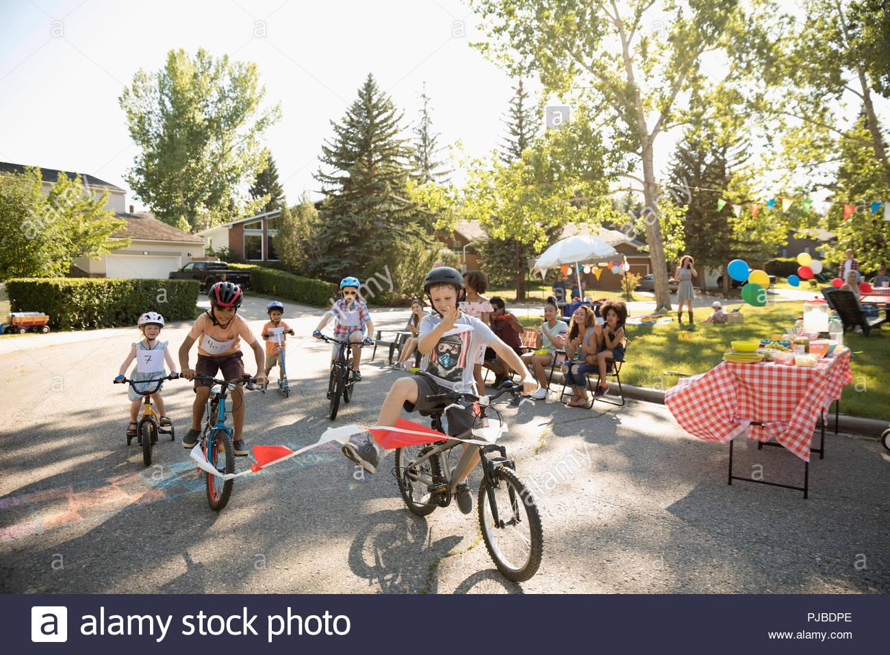 Kids enjoying bike race at summer neighborhood block party - Stock Image